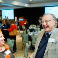 Guest laughing while chatting with two other guests at Scholarship Dinner 2019